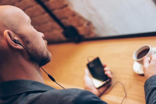 L'homme Au Casque à L'aide De Téléphone Portable, Assis Avec Un Café Au Café Photo Premium