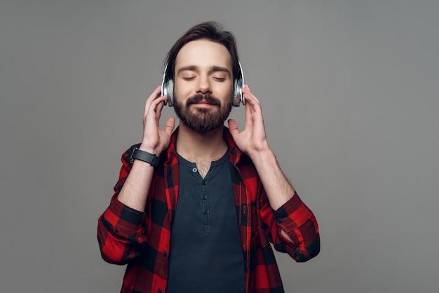 Un homme au casque écoute attentivement la musique. Photo Premium