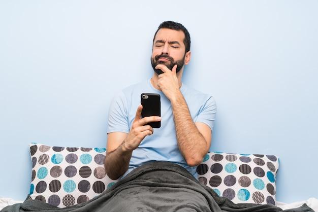 Homme au lit en train de penser et d'envoyer un message Photo Premium