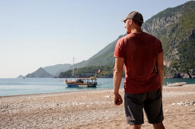 Homme aux épaules larges posant sur la plage turque Photo Premium