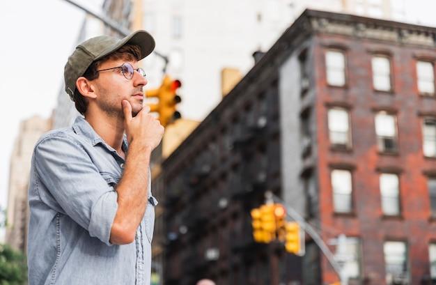 Homme aux lunettes soutenant son menton Photo gratuit