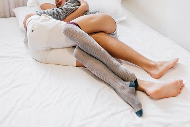 Homme Aux Pieds Nus Embrassant Sa Femme En Position Couchée Sur Des Draps Blancs Le Matin Photo gratuit