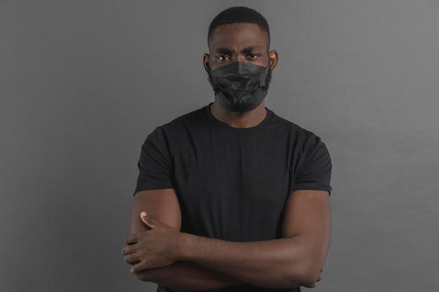 Homme Ayant Les Bras Croisés Et Portant Un Masque Photo gratuit