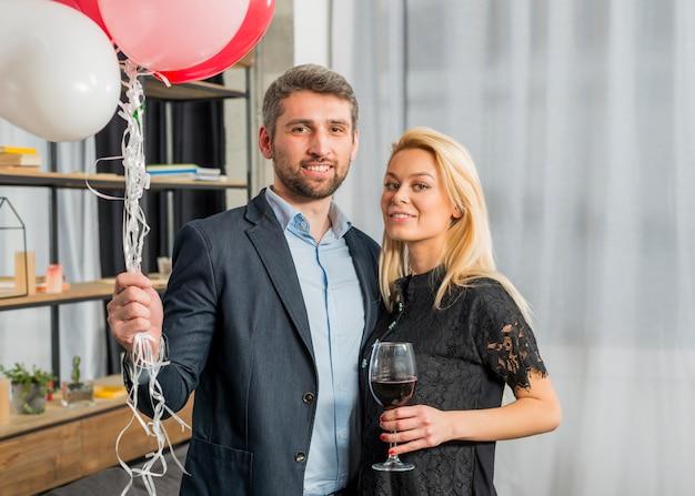 Homme avec des ballons près de femme avec verre de vin dans la chambre Photo gratuit