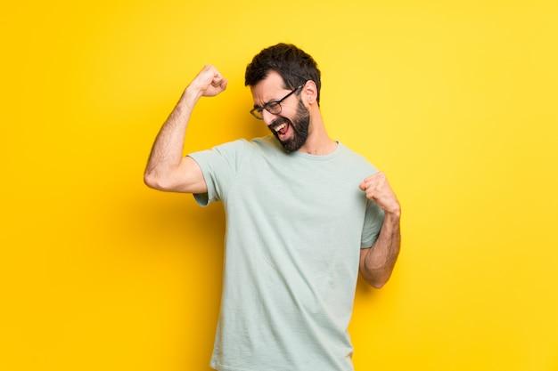 Homme à la barbe et à la chemise verte célébrant une victoire Photo Premium
