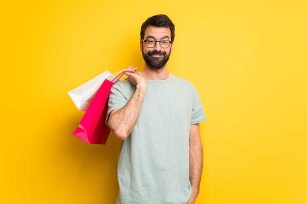 Homme à la barbe et chemise verte tenant beaucoup de sacs à provisions Photo Premium