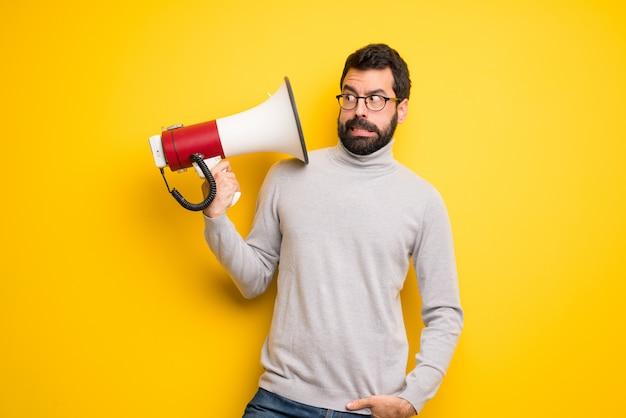 Homme avec barbe et col roulé prenant un mégaphone qui fait beaucoup de bruit Photo Premium