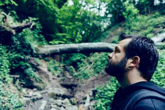 Homme à la barbe en levant dans la forêt Photo Premium