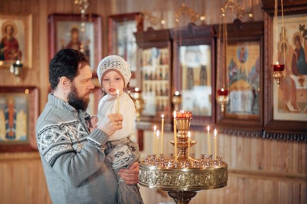 Un homme avec une barbe avec une petite fille dans ses bras se tient devant les icônes et prie dans l'église orthodoxe Photo Premium