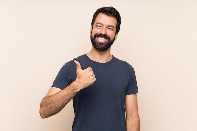 Homme à la barbe avec le pouce levé parce qu'il s'est passé quelque chose de bien Photo Premium