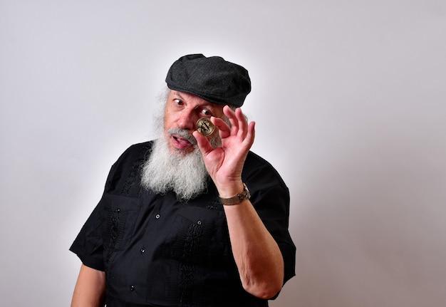 Homme Avec Barbe Tenant Un Bitcoin Et En Le Regardant Photo gratuit