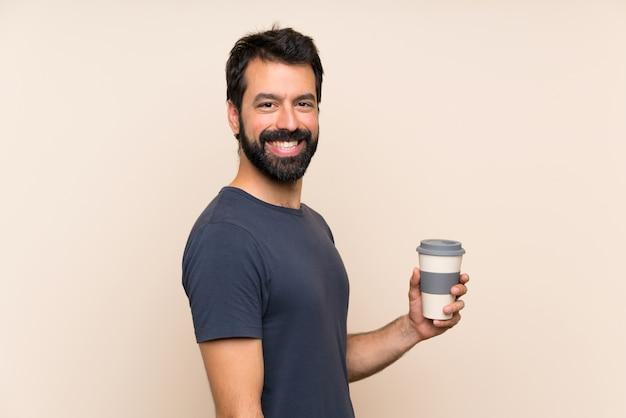 Homme à la barbe tenant un café avec une expression faciale surprise Photo Premium