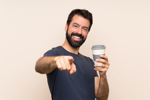 Homme à la barbe tenant un café pointe le doigt vers vous avec une expression confiante Photo Premium