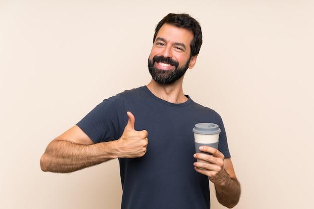 Homme à la barbe tenant un café avec le pouce levé parce que quelque chose de bien est arrivé Photo Premium