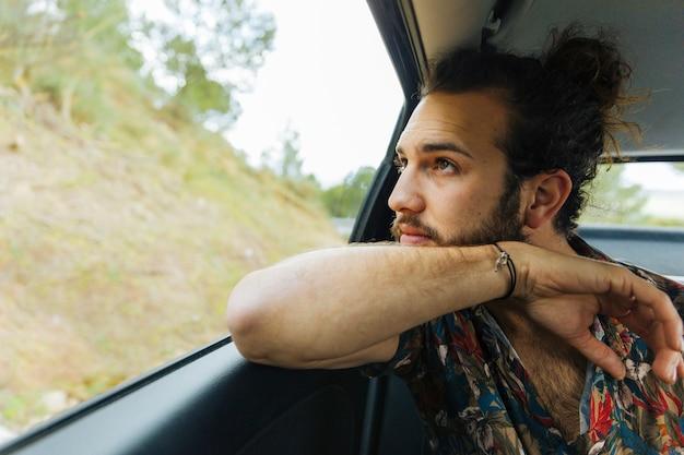 Homme barbu admirant les vues depuis la fenêtre de la voiture Photo gratuit