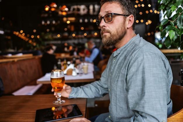 Homme Barbu D'âge Moyen Avec Des Lunettes Assis Dans Un Bar, Ayant Un Verre De Bière Légère Fraîche Après Le Travail Photo Premium