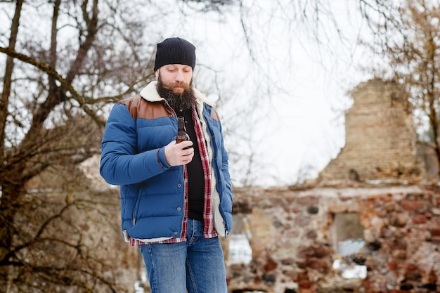 Homme barbu buvant de la bière en hiver dans la forêt Photo Premium
