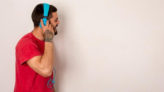 Homme barbu écoutant de la musique avec des écouteurs Photo gratuit