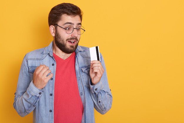 Un Homme Barbu étonné Habille Une Veste En Jean, Une Chemise Rouge Et Des Lunettes, Tenant Une Carte De Crédit Dans Les Mains Et Ressemble à Une Carte Avec Une Bouche Ouverte Photo gratuit