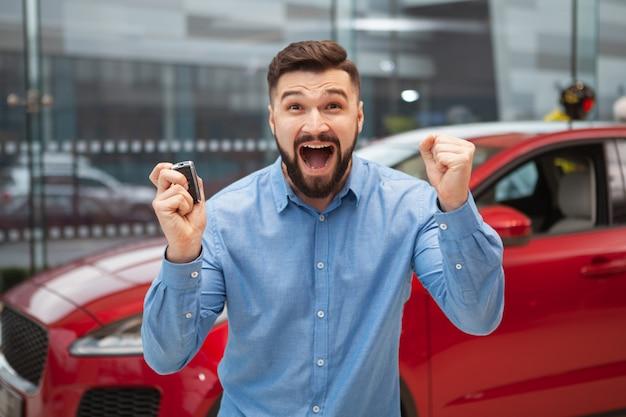 Homme Barbu Excité Hurlant Joyeusement, Tenant Les Clés De Sa Nouvelle Voiture. Photo Premium