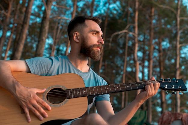 Homme barbu jouant de la guitare Photo gratuit