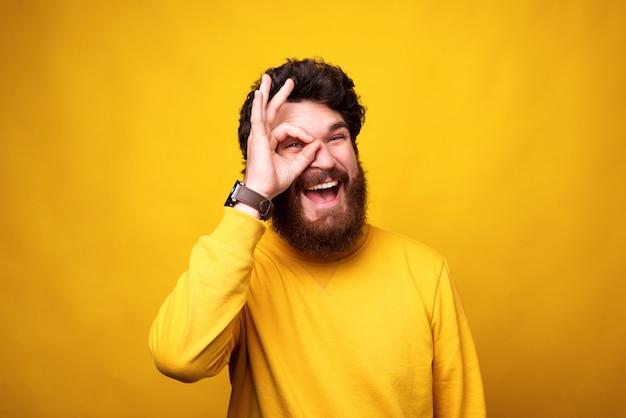 Un Homme Barbu Ludique Regarde La Caméra à Travers Un Geste Correct Sur Son œil. Photo Premium