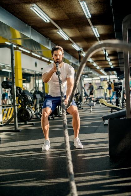 Homme Barbu Musclé Concentré Motivé Faisant Des Exercices De Corde De Combat Dans La Salle De Sport Moderne Ensoleillée. Photo Premium