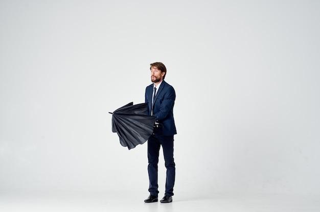 Homme Barbu Avec Un Parapluie Noir Et En Costume Sur Fond Clair En Pleine Croissance. Photo De Haute Qualité Photo Premium