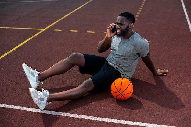 Homme barbu parlant au téléphone long shot Photo gratuit