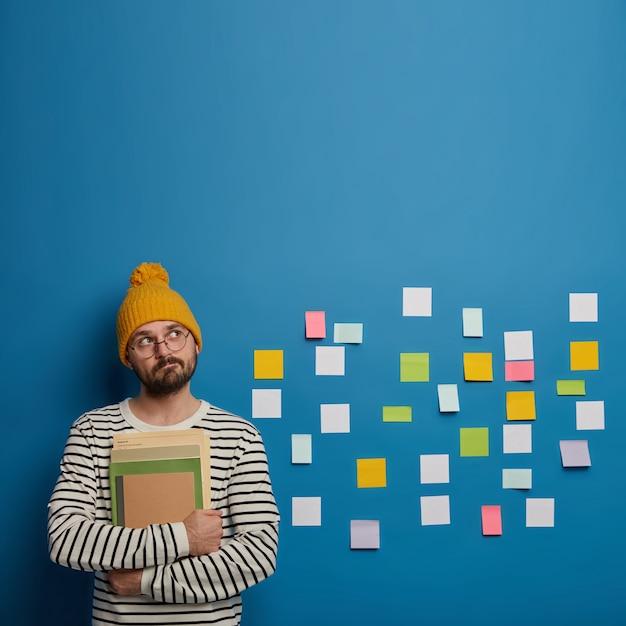 Un Homme Barbu Réfléchi Tient Des Livres, Regarde Pensivement Au-dessus, Réfléchit à La Façon De Créer Un Projet, Réfléchit à Différentes Idées Photo gratuit