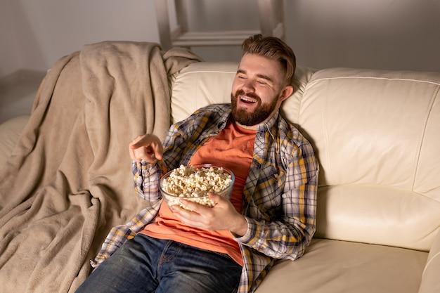 Homme Barbu Regardant Un Film Ou Des Jeux De Sport Tv Manger Du Pop-corn Dans La Maison La Nuit. Cinéma, Championnat Photo Premium