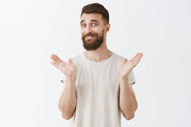 Homme Barbu Souriant Réticent Posant Contre Le Mur Blanc Photo gratuit