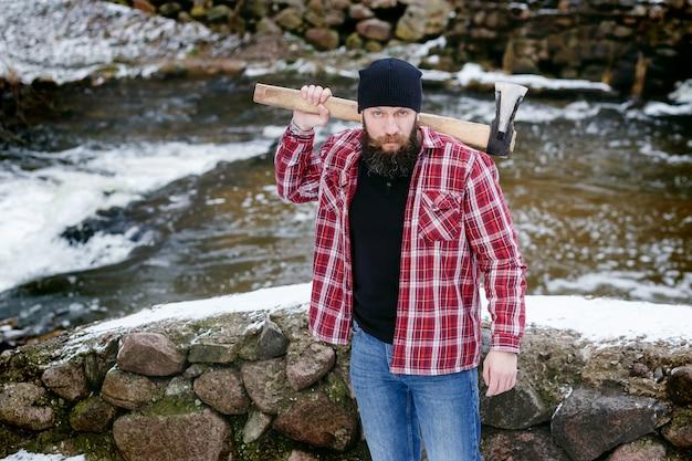 Homme barbu tenant dans ses mains une hache dans la forêt d'hiver Photo Premium