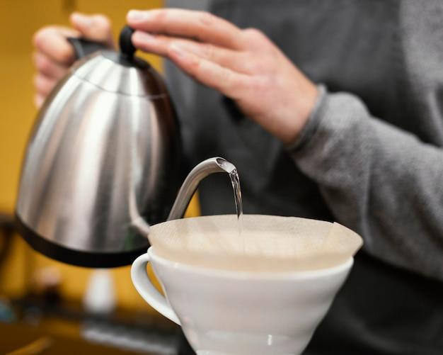 Homme Barista Avec Tablier Verser De L'eau Dans Le Filtre à Café Photo gratuit