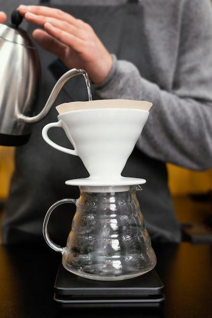 Homme Barista Verser De L'eau Dans Le Filtre à Café Photo gratuit