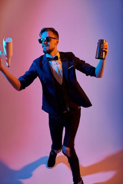 Homme barman jonglant bouteilles et tremblements, sur rose Photo Premium