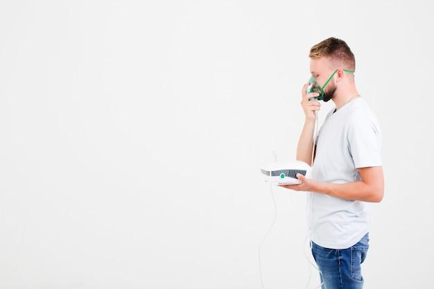 Homme en blanc avec nébuliseur d'asthme Photo gratuit