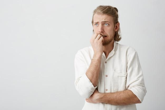 Homme Blond Attrayant Aux Yeux Bleus Et à La Barbe Qui Se Mord Les Ongles Photo gratuit