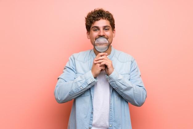 Homme blond au mur rose tenant une loupe Photo Premium