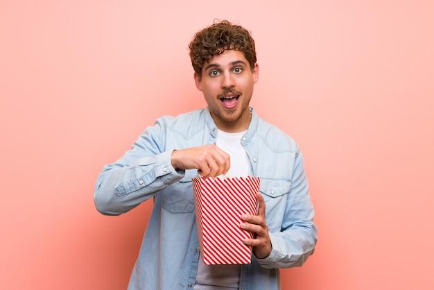 Homme blond sur mur rose surpris et mangeant des popcorns Photo Premium