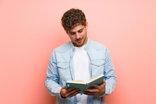 Homme blond sur mur rose tenant un livre et lire Photo Premium