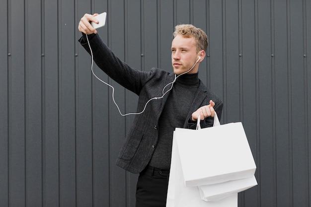 Homme blond en noir prenant un selfie avec smartphone Photo gratuit