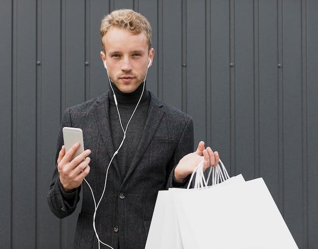 Homme blond en noir regardant vers la caméra Photo gratuit