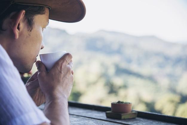 Homme boire du thé chaud avec fond de colline verte Photo gratuit