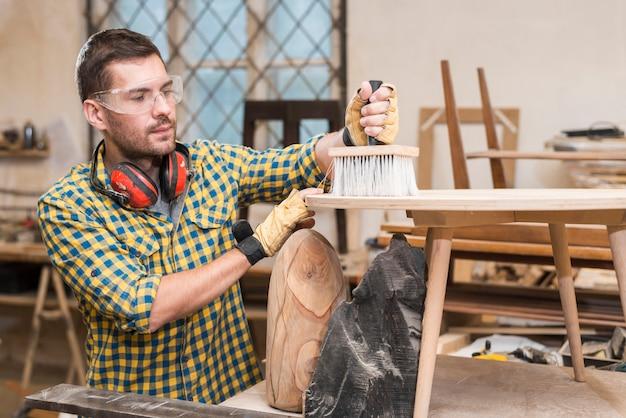 Homme, bois nettoyage, à, brosse poussière, sur, planche bois, dans, les, atelier Photo gratuit