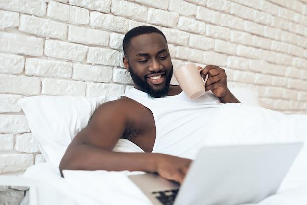 L'homme boit du café au lit tout en travaillant avec un ordinateur portable. Photo Premium