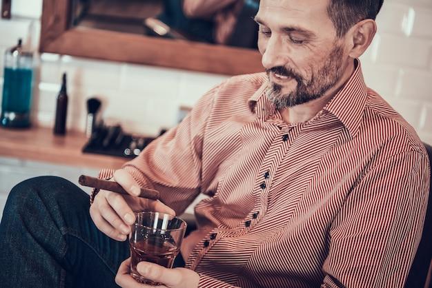 Un homme boit du whisky et fume une cigarette dans un salon de coiffure Photo Premium
