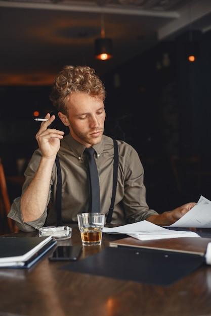 L'homme Boit Du Whisky. Homme D'affaires Lit Des Documents. Réalisateur En Chemise Et Bretelles. Photo gratuit