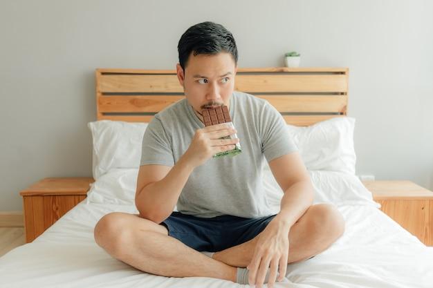 L'homme boit une tasse de café sur le lit dans sa chambre. Photo Premium