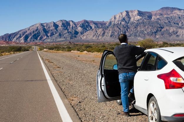 Homme Sur Le Bord De La Route En Appréciant Le Paysage Photo gratuit